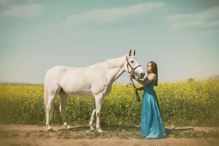Young, red-haired woman  in elegant long dress walking with her beautiful horse thought yellow field of rapeseed Reklamní fotografie