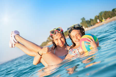 Two young girls with snorkeling equipment having fun in sea water. Ready for snorkeling adventure