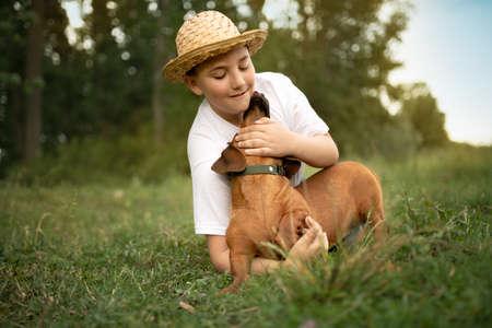 Teen boy on grass playing with dog, my pet my best friend Foto de archivo