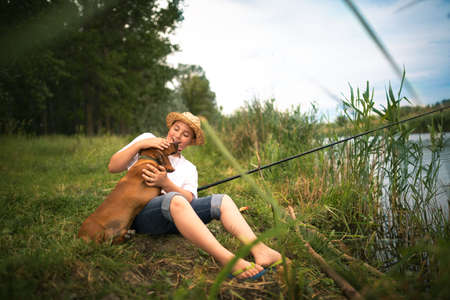 Young fisher cuddle his favorite pet , sitting on grass next lake