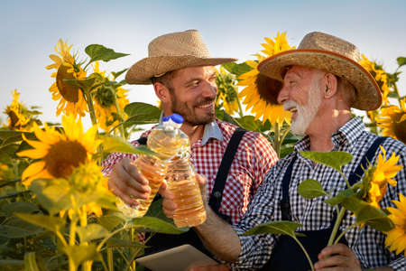 Smiling senior farmer with son proud on organic sunflower oil product of their farm
