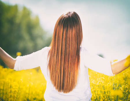 Happiness, spring. Girl in yellow meadow