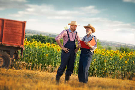 Two farmers looking at data from clipboard on the farm, Portrait of two farmers proud of their farm