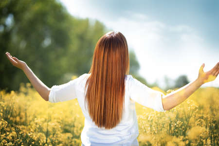 Redhead woman enjoying in beautiful yellow rapeseed field