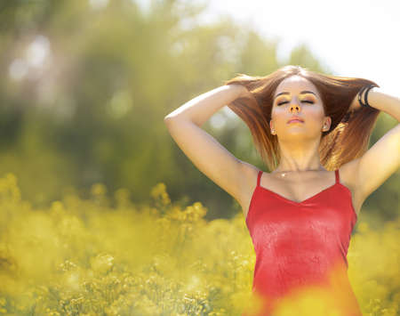 Young woman touching her long red hair and standing in field of flowers Foto de archivo
