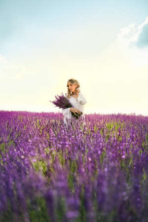 Beautiful young woman relaxing in lavender field and hugging bouquet of lavender flowers