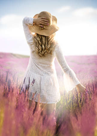 Blond long haired girl in lavender field in straw hat and white long dress on fairy field of lavender Foto de archivo