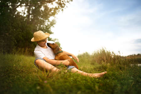 Cute boy who gives his puppy a big hug. The child and his best animal friend sitting on a grass in nature Foto de archivo