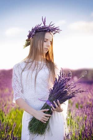 Portrait of beautiful romantic woman in fairy field of lavender with bouquet Foto de archivo