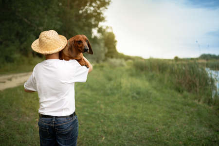 Boy with straw hat carrying his dog on shoulder, back view Foto de archivo