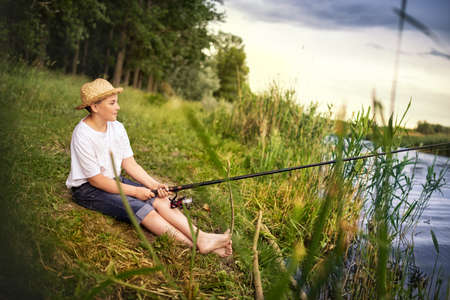 Barefoot teen boy holding fishing rod and looking in river, waiting for a catch Banco de Imagens
