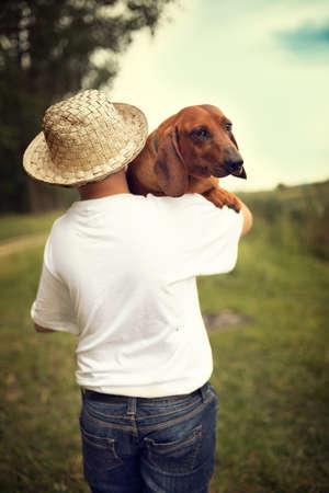 Teenage boy carrying his pet dachshund dog on field Foto de archivo - 154726067