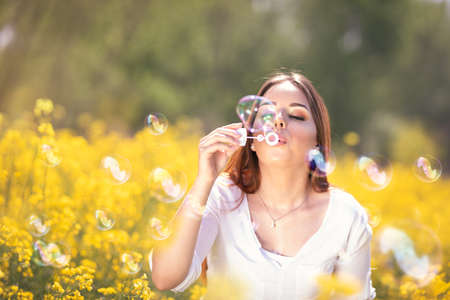 Young beautiful woman blowing soap bubbles in the spring blossom field. Spring leisure time. Positive and happy people. Foto de archivo - 154726068