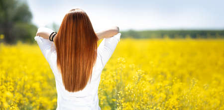 Beautiful long hair. Beauty with luxurious straight red hair in yellow flowers.  Lady with long smooth shiny straight hair. Hairstyle, cure Foto de archivo - 154726105