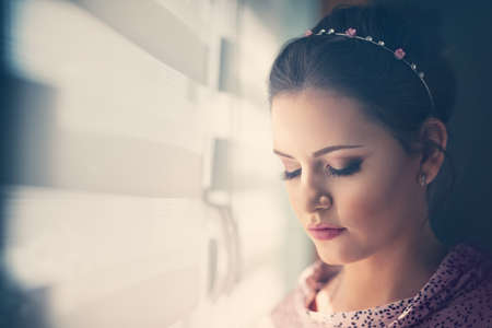 Beautiful young woman with modern hairstyle next window Foto de archivo - 154726140
