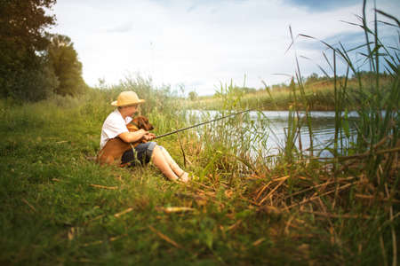 Teen boy with dachshund on fishing outside on a lake in the summer Foto de archivo
