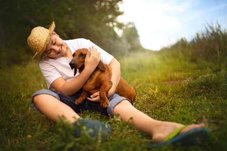 Young teen boy playing with his dachshund. They on grass and hugging. Foto de archivo