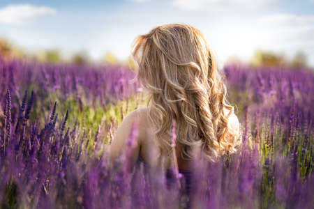 A beautiful young woman standing in the middle of a lavender field in the golden light of the sunset enjoying her hair Foto de archivo - 154726158