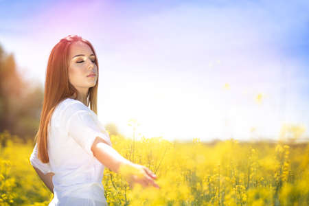 Peaceful woman walking through blooming rapeseed field and touching flowers