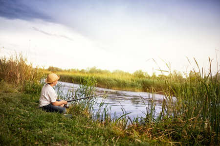 Kid fisherman sitting on grass on shore and waiting for a catch