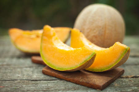 Fresh cantaloupe cut into pieces on wooden table.
