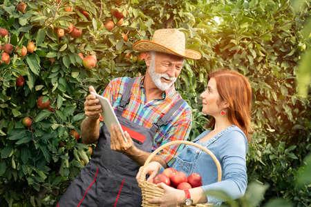 Senior farmer holding digital tablet and showing his daughter e-order from customer Foto de archivo - 154726212