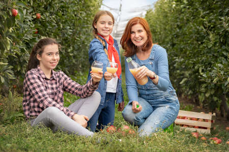 Smiling young family with 100% organic apple juice in apple orchard