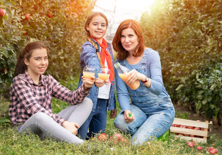 Young woman holds a bottle with natural organic juice, produced from the garden on a sunny sunset, next to blonde girls with glasses full juice. Foto de archivo - 154726393
