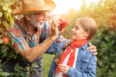 Bearded older man having fun with her cute freckled granddaughter Foto de archivo