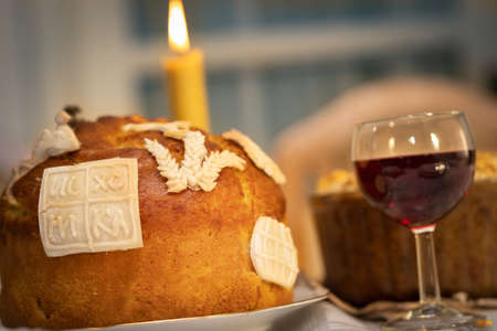 Slava cake decoration with red wine and candle on a ceremoniously set table