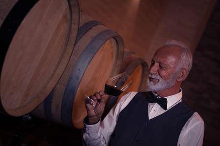 senior man wine tasting in a wine cellar