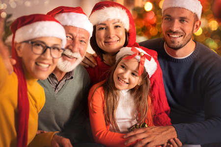 Family multi-generation in Santa hats, smiling and celebrating Christmas together Archivio Fotografico