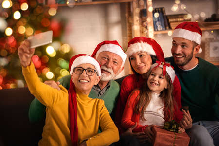 Happy senior couple with children and granddaughter take selfie