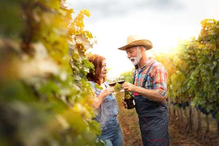 Winemaker enjoy in taste of their wine standing in autumn vineyard