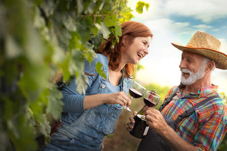 Happy couple winemaker with wineglass in the vineyard. Farmers drinking red wine