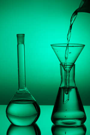 milliliters: Laboratory glassware on color background on the table. Stock Photo