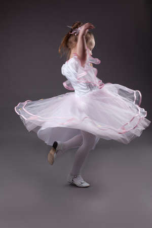 Little girl dancing in studio wearing light chiffon dress, over gray background Stock Photo