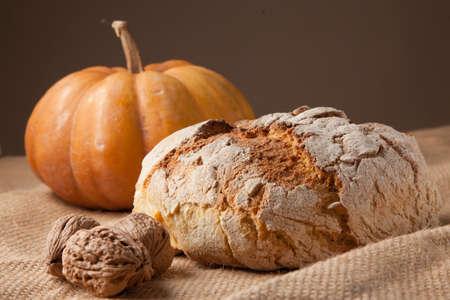 rustic autumn still life with bread pumkin walnuts.