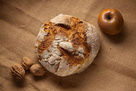 rustic autumn still life with bread apple walnuts.