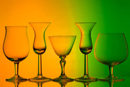 silhouette of wine glasses on orange and green background with space for text Stock Photo