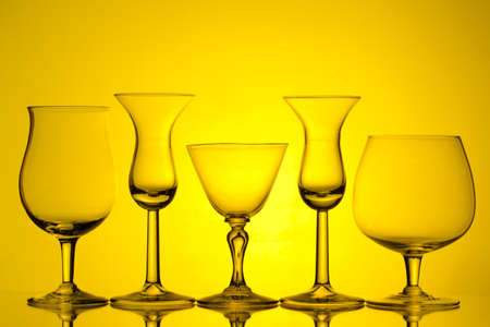 silhouette of wine glasses on yellow background with space for text Stock Photo