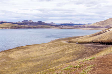 Lonely car driving on a road to Landmannalaugar, Iceland Stock Photo