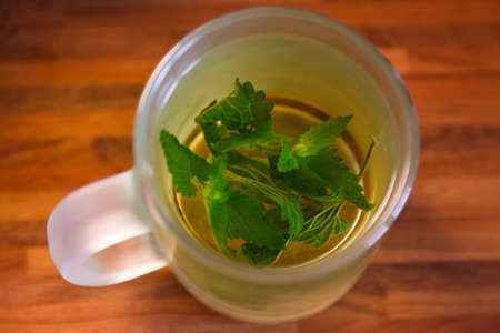 cup of black tea with mint leaves on a wooden table