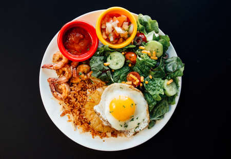 Asian Pineapple fried rice with various vegetables on a white plate and black background