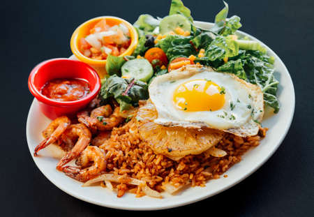 Close up image of Asian pineapple fried rice with fried egg,shrimp,and vegetables salad on a white plate 版權商用圖片