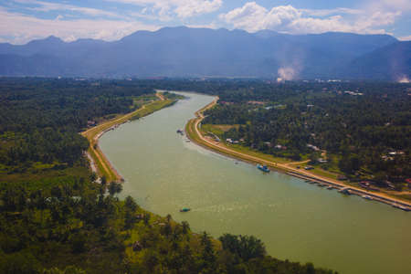 River by a town with mountains in the background Standard-Bild