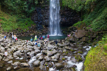 People relaxing by a waterfall Editorial
