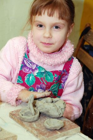 herself: child playing with clay