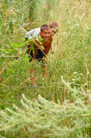playing boys in long grass Stock Photo - 4809553