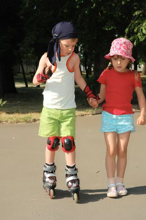 helping children: Friendly support. Rollerblading. Stock Photo